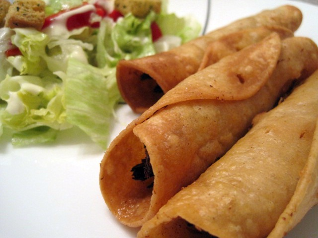 Homemade chicken flautas served with a salad.