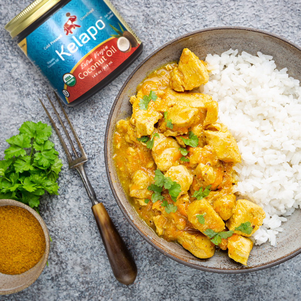 coconut curry in bowl next to kelapo coconut oil