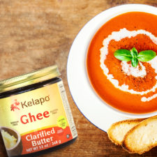 bowl of creamy tomato basil soup topped with basil and a side of baguette sitting next to a jar of kelapo ghee